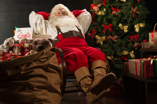 Santa Claus keeping his hands behind head while relaxing at home sitting in comfortable armchair near christmas tree drinking milk and eating fresh cookies. For Santa sin on table