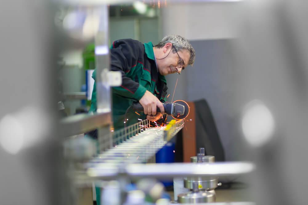 Industrial-worker-in-manufacturing-plant-grinding-steel